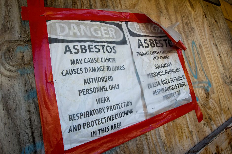 Asbestos warnings posted on the outside of the former Meriden-Wallingford Hospital building in Meriden, Thursday, October 6, 2016. | Dave Zajac, Record-Journal