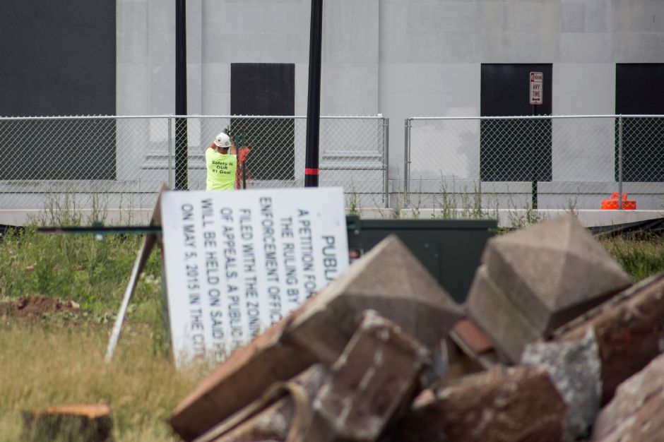 A worker puts up fencing along Church Street as construction begins at the 24 Colony St. site Thursday June 18, 2015. | Richie Rathsack/Record-Journal
