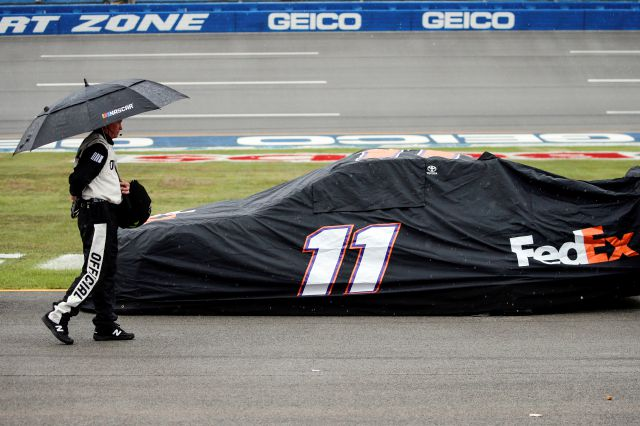 An official walks by the car of Denny Hamlin (11) car during a rain delay in a NASCAR Cup Series auto race at Talladega Superspeedway in Talladega, Ala., Sunday, Oct. 13, 2019. (AP Photo/Butch Dill)