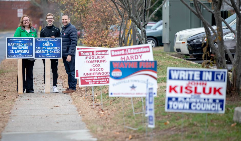 From left, Crystal St. Lawrence, Connor and Todd Cello hold campaign signs outside Linden Street School during the Nov. 5, 2019 Plainville municipal election. St. Lawrence was one of six Democrats elected to the Board of Education, flipping control from Republican to Democrat. | Devin Leith-Yessian/Plainville Citizen