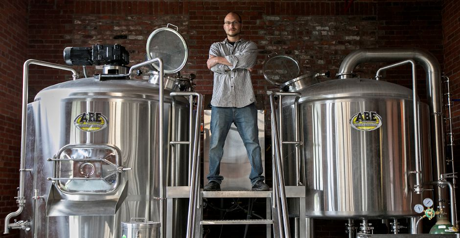 Josh Norris, co-owner of Witchdoctor Brewing Company, stands on the brewhouse of the business in Factory Square on Center Street in Southington, Wednesday, April 26, 2017. | Dave Zajac, Record-Journal