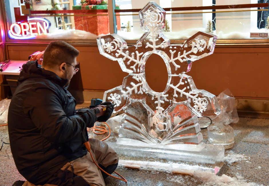 Matt Terzano of Ice Matters carves a snowflake design in ice in front of the Main Street Market during the 9th annual Holiday Stroll in downtown Wallingford on Friday, Dec. 1, 2017. | Bailey Wright, Record-Journal
