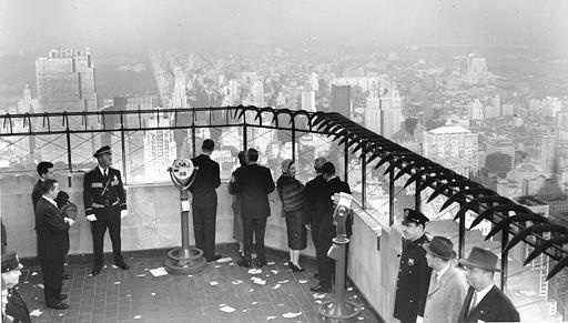 "Queen Elizabeth II, wearing mink stole, and Prince Philip, standing next to viewing telescope, view New York City from the observatory roof of the Empire State Building on Oct. 21, 1957. The Queen said, ""It"