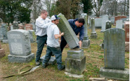 Rosenbloom Monument Co. workers from left, Nathan Fohne, Derek Doolin and Philip Weiss hoist a headstone at the Chesed Shel Emeth Cemetery in University City, Mo., where over 150 headstones were tipped over. The cemetery is getting a show of support from cleanup volunteers, well-wishers and financial contributors from across many faiths. (AP Photo/Jim Salter)
