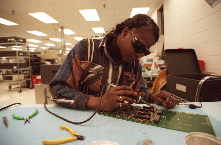 RJ file photo - Jettie Brackett, of Meriden, works on a board at DNE Technologies in Wallingford that will go into a multiplexer -- a device that allows the military to compress a signal when sending it to a satellite. It is also used in a similar commercial device, Jan. 1999.