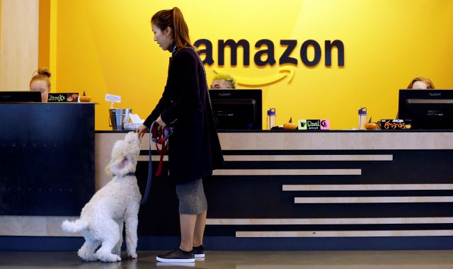 FILE - In this Wednesday, Oct. 11, 2017, file photo, an Amazon employee gives her dog a biscuit as the pair head into a company building, where dogs are welcome, in Seattle. Amazon announced Thursday, Jan. 18, 2018, that it has narrowed its hunt for a second headquarters to 20 locations, concentrated among cities in the U.S. East and Midwest. Toronto made the list as well, keeping the company's international options open. (AP Photo/Elaine Thompson, File)
