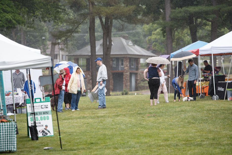 Fair goers take shelter during a rain shower Saturday during the Pet Fair and 5K in Hubbard Park Meriden June 23, 2018 | Justin Weekes / Special to the Record-Journal