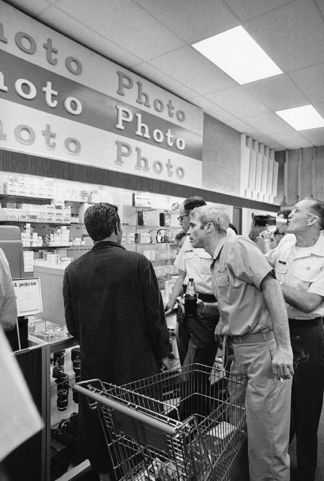 Navy Lt. Cmdr. John McCain III peers at camera counter during shopping tour on Friday, March 16,1973 at Clark Air Base exchange. McCain, son of the former commander-in chief of the Pacific Fleet, was released by the North Vietnamese in Hanoi Wednesday. (AP Photo/GT)