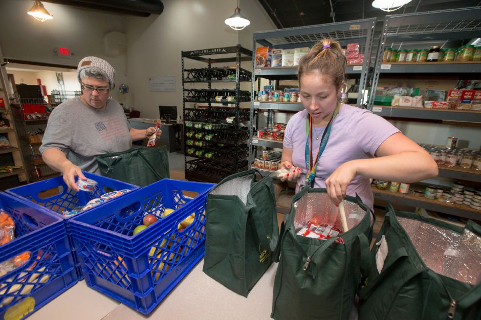 Lisa Teodosio from Rocky Hill Elementary School, left, and Kimberly Dunnigan of Cook Hill Elementary School sort their food deliveries Friday at Master