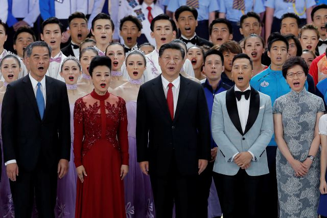 FILE - In this Friday, June 30, 2017, file photo, Chinese President Xi Jinping, center, sings with Hong Kong Chief Executive Leung Chun-ying, left, Chief Executive-elect Carrie Lam, right, and Hong Kong artists during the grand variety show as part of a ceremony marking the 20th anniversary of the Hong Kong handover to China in Hong Kong. (AP Photo/Kin Cheung, File)
