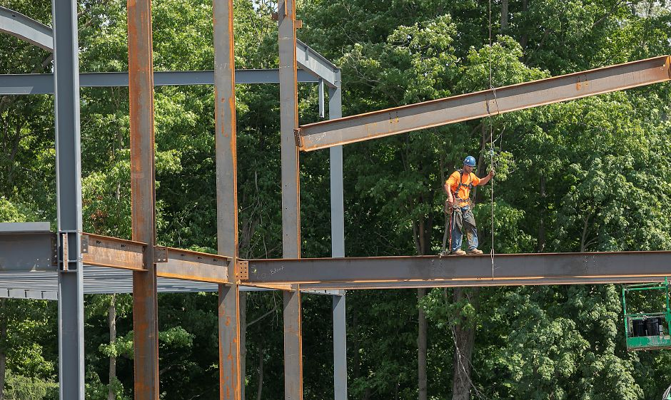 A worker helps maneuver a beam into place on the Hartford HealthCare medical facility under construction on South Main Street in Cheshire, Wednesday, August 15, 2018. Dave Zajac, Record-Journal