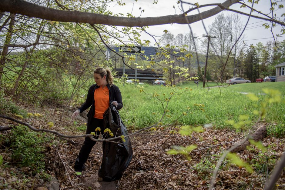 MERIDIAN, CONNECTICUT - 05/05/2018: Shelby Verrone-Webb cleans litter from the street and highway exit ramp near Preston Avenue. Meriden Mayor Scarpati and the Council of Neighborhoods put on their annual Mayor