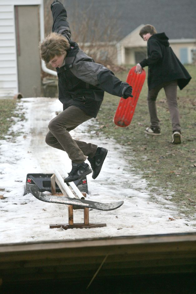 Ryan Greenwood, 17, jumps his snowboard off the rail lined with snow in the backyard of his Wallingford home Friday afternoon January 19, 2007. Ryan Greenwood, his brother Steven Greenwood, 19, and their friend Andy Novak made their own snow using an air compressor and a garden hose. On the right is friend Andy Novak. Chris Angileri/Record-Journal.