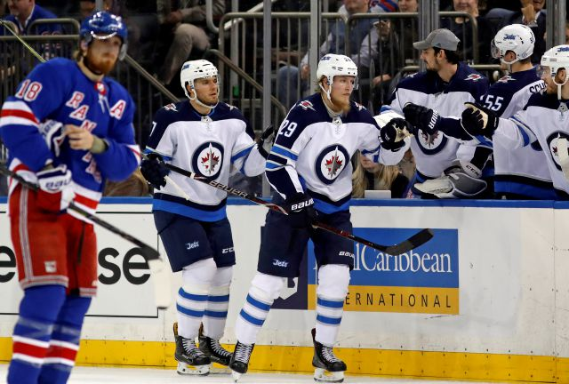Winnipeg Jets teammates greet Jets defenseman Ben Chiarot (7) and Jets right wing Patrik Laine (29) of Finland who scored his second goal during the second period of an NHL hockey game against the New York Rangers in New York, Tuesday, March 6, 2018. New York Rangers defenseman Marc Staal (18) skates past, left. (AP Photo/Kathy Willens)