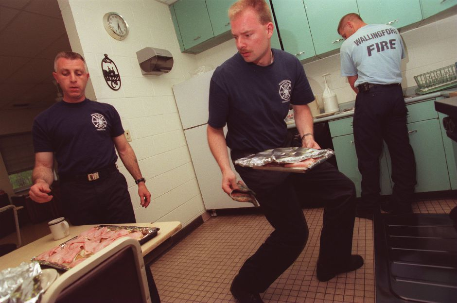 RJ file photo - Jack Kroczek, center, a newly hired Wallingford firefighter, looks for a spot on the table to place his oven-heated chicken cordon bleu dinners, May 1999. As a rookie, Kruczek has to pull kitchen duty, cooking for the others at the station house. Inspecting his culinary art is firefighter Walt Sckrenker, left.