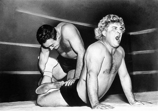 "George Wagner, Hollywood wrestler, got his hair mussed during a match with Marvin Mercer at Washington on Nov. 17, 1948. Although the ""pretty one"" registers anguish, he won the match. (AP Photo/Bill Ingraham)"