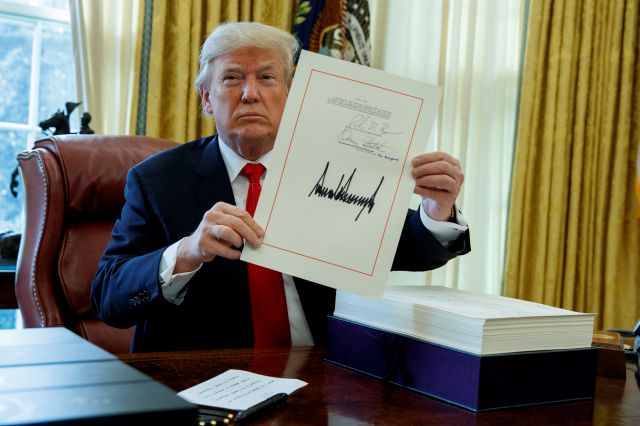 President Donald Trump shows off the tax bill after signing it in the Oval Office of the White House, Friday, Dec. 22, 2017, in Washington. (AP Photo/Evan Vucci)