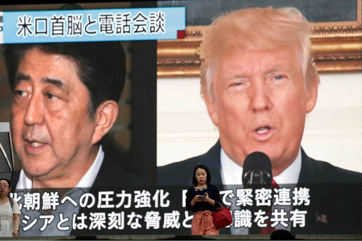 People walk by a TV news program showing the images of Japanese Prime Minister Shinzo Abe, left, and U.S. President Donald Trump while reporting North Korea
