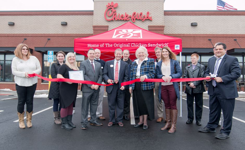 Mike Hartman, center with scissors, cuts the ribbon at the Southington Chick-Fil-A opening ceremony on Thursday. The Queen Street store is Hartman