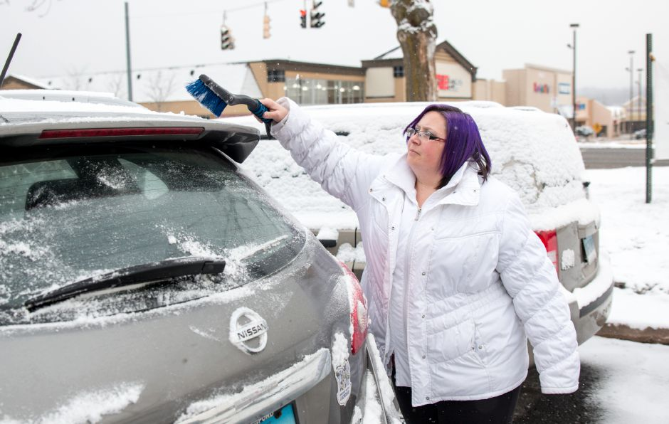 April Weavey, of Meriden, clears snow off her car during Saturday