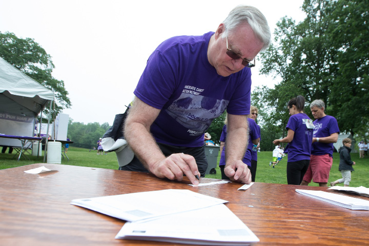 Rob Johnson of Cromwell fills out a registration form Saturday during the PurpleStride 5k and walk fundraiser for Pancreatic Cancer Action Network at Hubbard Park in Meriden Jun. 17, 2017 | Justin Weekes / For the Record-Journal