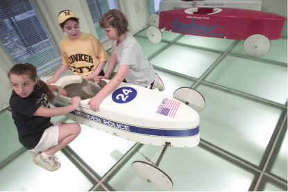 File photo - Rebecca Parker, 10, second from left, shows her soap box car to friend Abbey Rowe,10, as Kaley Kiss,9, far left, is called next to the weigh in area at Curtis Cultural Center in Meriden Wednesday evening June 11, 2003.