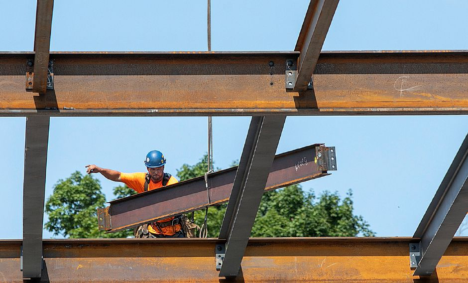 A worker helps a crane operator guide a beam into place as construction continues on the Hartford HealthCare medical facility on South Main Street in Cheshire, Wednesday, August 15, 2018. Dave Zajac, Record-Journal