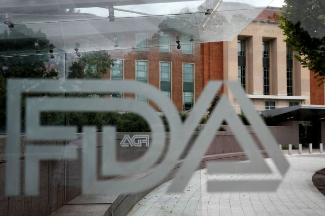 This Aug. 2, 2018, file photo shows the U.S. Food and Drug Administration building behind FDA logos at a bus stop on the agency