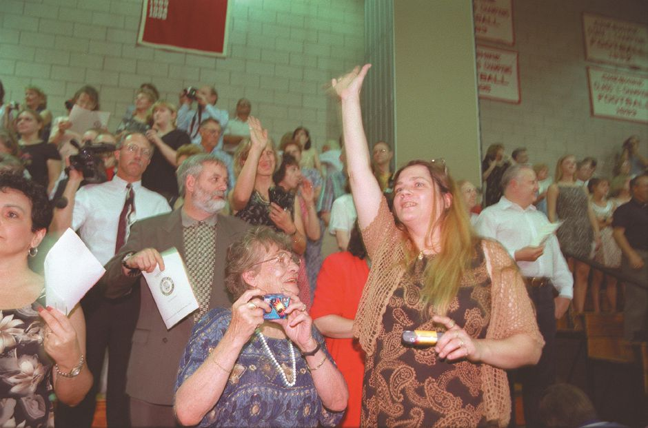 RJ file photo - Elizabeth Vincent, right, mother of graduating senior Daniel Vincent, spots a familiar face at teh Cheshire High School graduation June 16, 1998. Patricia Gliday, center, grandmother of the graduate, prepares to snap pictures of the special occasion.
