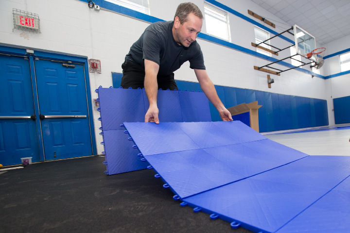 Kevin Wheelock of Mateflex lays border tiles at Ulbrich Boys & Girls Club.