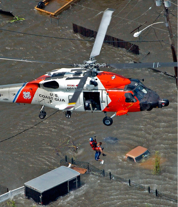 FILE - In this Tuesday, Aug. 30, 2005 picture, a New Orleans resident is rescued from the rooftop of a home by a U.S. Coast Guard helicopter crew as floodwaters from Hurricane Katrina cover the streets. (AP Photo/David J. Phillip)