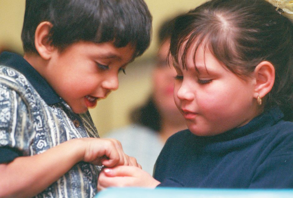 RJ file photo - During the Three Kings Day celebration at the Meriden Public Library Jan. 10, 1999, Jose Delgado, 5, and his sister Maryanne, 9, argue over a handful of candies before realizing they are being photographed.