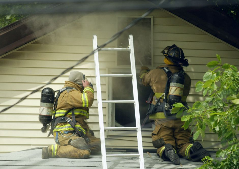 Meriden Truck 1 firefighters Dan Lyons, left, and Ryan Dunn ventilate the attic of an apartment at 88 Olive Street after a fire broke out in the kitchen on the second floor Friday afternoon. A woman and three small children living on the second floor were relocated by the Red Cross.