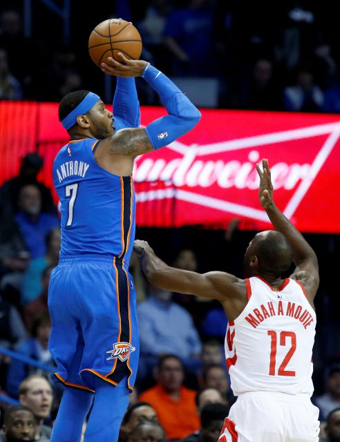 Oklahoma City Thunder forward Carmelo Anthony (7) shoots over Houston Rockets forward Luc Mbah a Moute (12) in the first half of an NBA basketball game in Oklahoma City, Tuesday, March 6, 2018. (AP Photo/Sue Ogrocki)