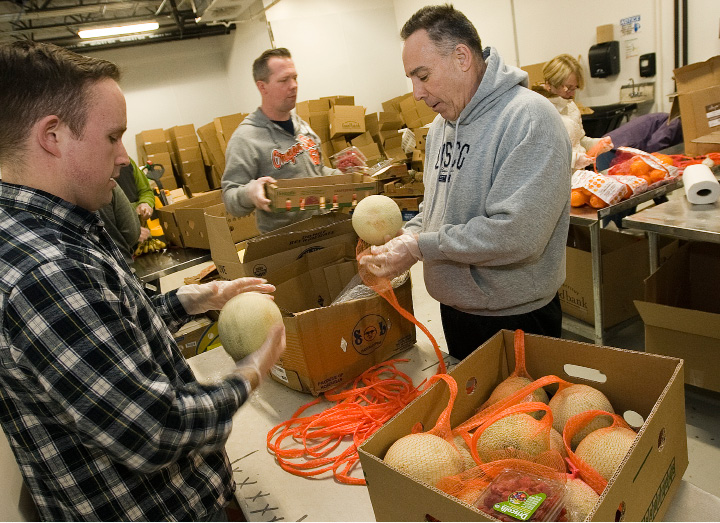 U.S. Coast Guard New Haven volunteers, left to right, Tyler Bittner, Brian Drake and Joe Cieslik sort fruit at the new Connecticut Food Bank at 2 Research Parkway, across from Bristol-Myers Squibb in Wallingford, Tuesday, February 2, 2016. The non-profit will hold an open house Thursday, welcoming the community to learn about the new facility.  |  Dave Zajac / Record-Journal
