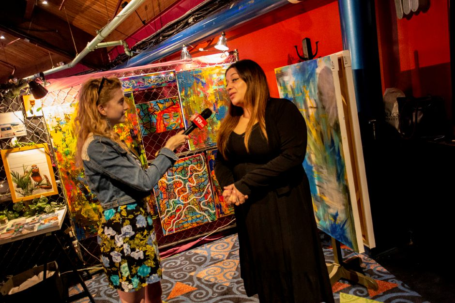 Record-Journal Digital Content Producer Ashley Kus talks with Cierra Serrano about her artwork on display at the RAW Artist showcase at the Oakdale Theatre in Wallingford July 18, 2018. | Richie Rathsack, Record-Journal