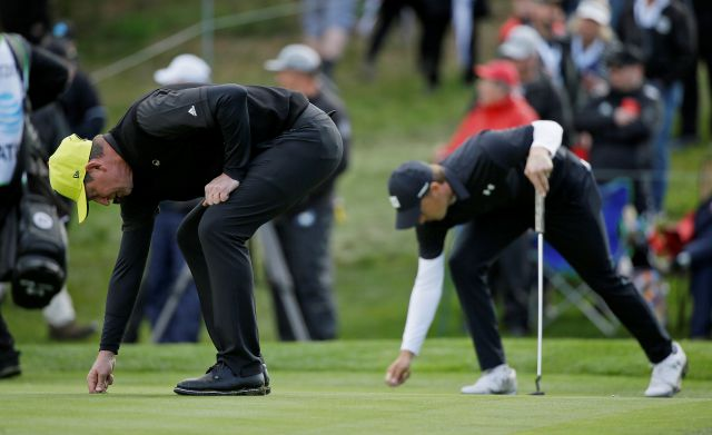 Wayne Gretzky, left, and Jordan Spieth, right, repair their marks on the 17th green of the Spyglass Hill Golf Course during the second round of the AT&T Pebble Beach Pro-Am golf tournament Friday, Feb. 8, 2019, in Pebble Beach, Calif. (AP Photo/Eric Risberg)