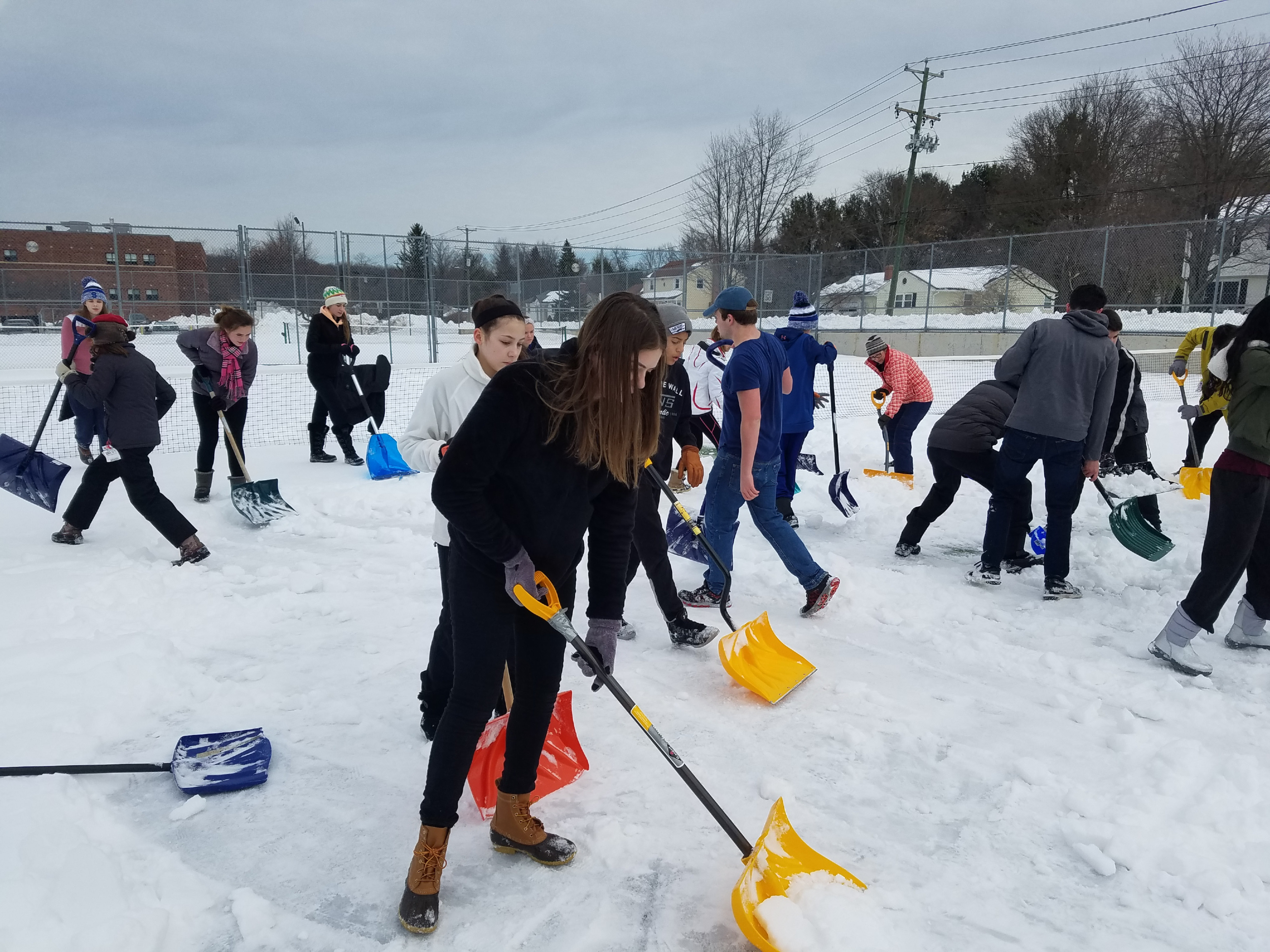 Members of the Southington tennis teams, with some help from parents and volunteers, clear snow from the Southington High School tennis courts on Monday.  Video at Myrecordjournal.com| Photos courtesy of Robin Thompson