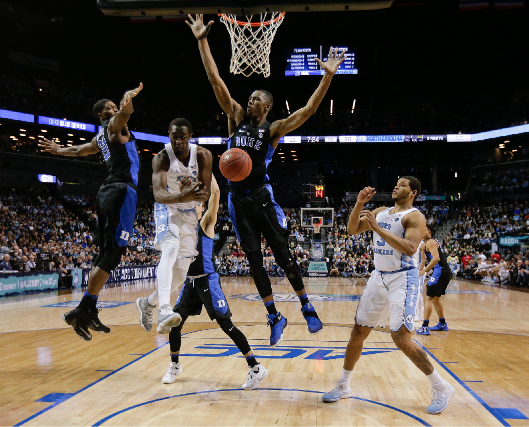 North Carolina forward Theo Pinson (1) passes off the ball to forward Kennedy Meeks (3) against Duke forward Amile Jefferson (21) and forward Harry Giles (1) in the first half of an NCAA college basketball game during the semifinals of the Atlantic Coast Conference tournament, Friday, March 10, 2017, in New York. (AP Photo/Julie Jacobson)