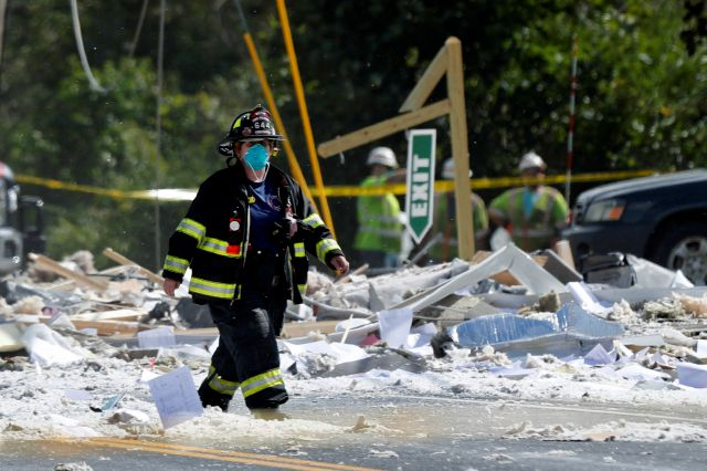 A firefighter walks through the scene of an explosion Monday, Sept. 16, 209, in Farmington, Maine. Officials say a town