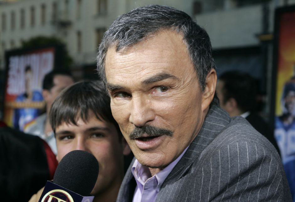 "Actor Burt Reynolds, right, who stars in the movie ""The Longest Yard"", gets interviewed after arriving for the movie"