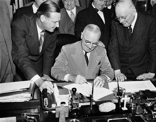 Pres. Harry Truman, seated at center, signs legislation raising the minimum wage from 40 to 75 cents, Oct. 26, 1949, Washington, D.C. Observing the signing are Maurice Tobin, left, Secretary of Labor, and William Green, right, president of the American Federation of Labor. Others are unidentified. (AP Photo)