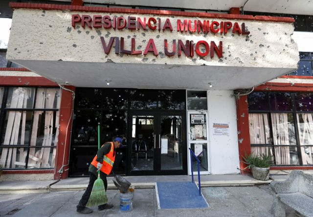A worker cleans up Monday outside City Hall, riddled with bullet holes, in Villa Union, Mexico. The small town near the U.S.-Mexico border began cleaning up after 22 people were killed in a weekend gunbattle between a heavily armed drug cartel assault group and security forces. Eduardo Verdugo, Associated Press