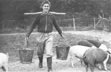 Miss Marcelle Guanziroli, an actress in regular life, steps in a new tempo with Britain in the war. Here she is feeding pigs on a farm as England sent its manpower to the front  Oct. 22, 1939. (AP Photo)