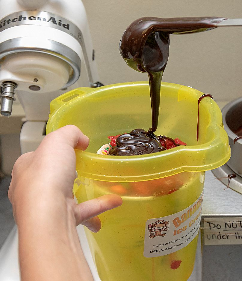 Hot fudge is added to a Gone Bananas bucket sundae.