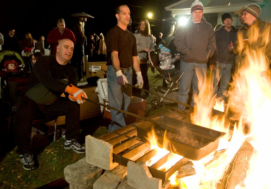 From left: Faith Living Church members Jim Lami and Mike Zullo roast pants of chestnuts over a bonfire outside the Faith Living Church during the Christmas in the Village event in downtown Plantsville, December 1, 2011. (Sarah Nathan/Record-Journal)
