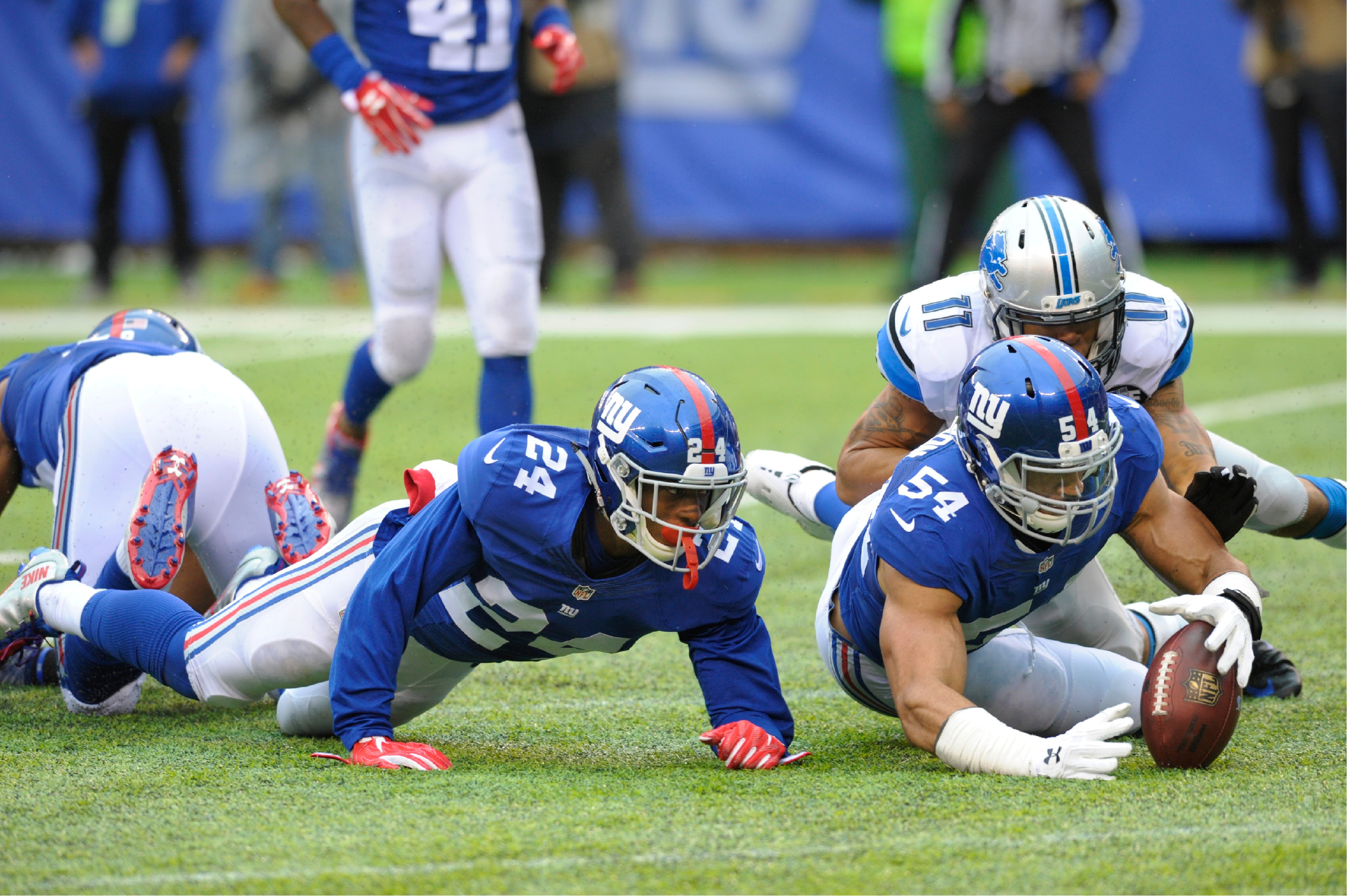 New York Giants defensive end Olivier Vernon (54) recovers a fumble as Detroit Lions wide receiver Marvin Jones (11) and Eli Apple (24) close in during the first half of an NFL football game Sunday, Dec. 18, 2016, in East Rutherford, N.J. (AP Photo/Bill Kostroun)
