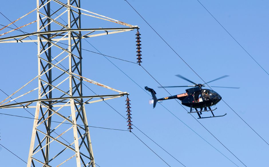 A helicopter crew from Pennsylvania based Haverfield Aviation, inspects transmission lines near Underpass Used Auto Parts in Wallingford, Tuesday, August 23, 2016. Frank Poirot, a spokesman for Eversource Energy, said the crew will be flying over lines in the central and northeastern part of the state over the next few weeks. | Dave Zajac, Record-Journal