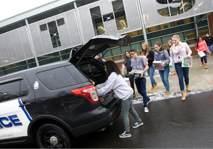 Students pack a police vehicle with toys during Wilcox Tech