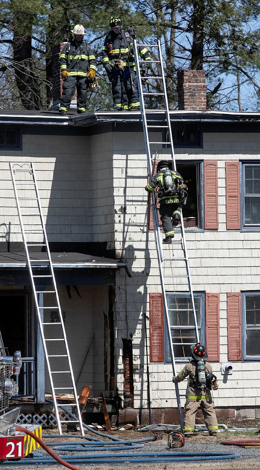 Firefighters descend the roof  at 764 Marion Ave. in Southington after putting out a fire there on Monday.